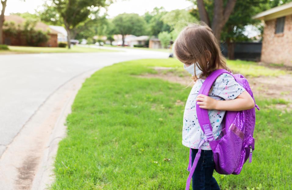 little girl waiting for bus